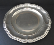 Round silver tray with wavy border and coat of arm