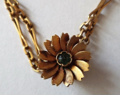 A gold long chain with a flower
