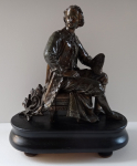 Statue of a sitting painter on a stool