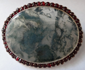 Silver brooch with algae and garnet frame