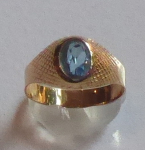 Golden ring with engraved grid and blue stone