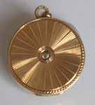 Round gold opening medallion, engraved, with clear stone