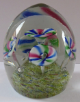 Smaller glass paperweight with five annealed flowers