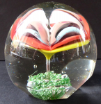 Round, domed paperweight with colored large flower