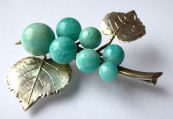 Silver brooch, twig with leaves, and aventurines