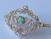Golden brooch with diamonds and emerald